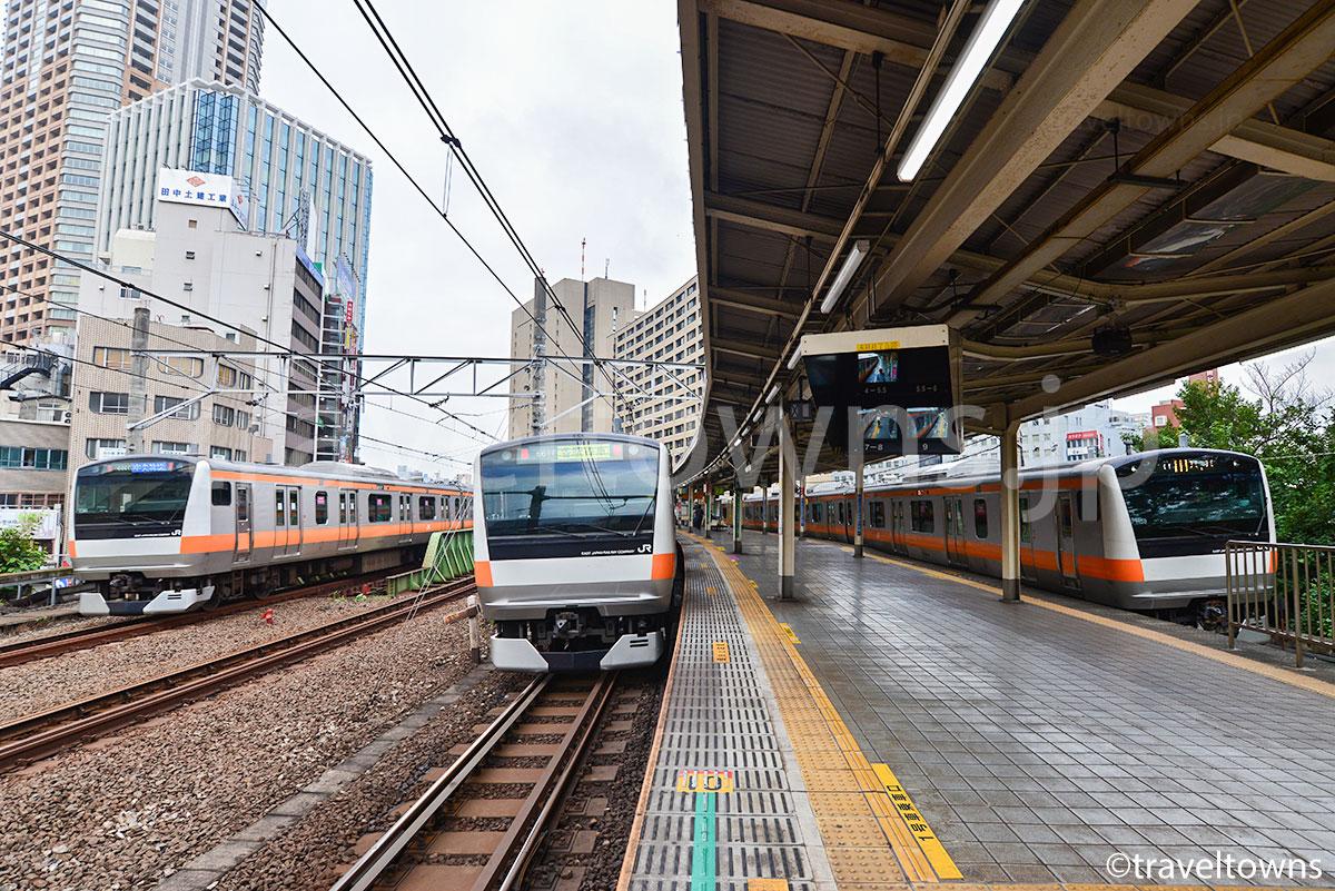 早朝の飯田橋駅に停車中するJR中央線の各駅停車と通過する中央特快